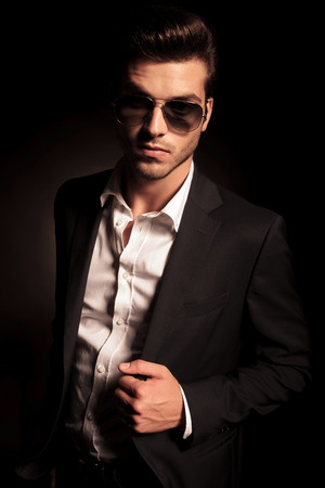 cool young man in suit and sunglasses posing on black studio background photo
