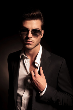 portrait of a sexy man in suit and sunglasses holding his suit by collar on black background photo
