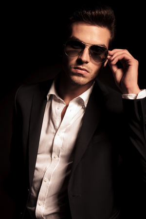 suit man: portrait of a sexy young fashion man putting on his sunglasses on black background