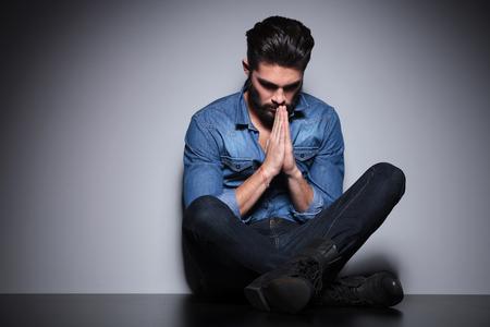 hombre orando: Hermoso hombre en camisa azul sentado y rezando