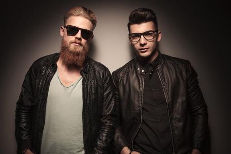 coiffer: Deux mecs chauds dans veste en cuir avec des lunettes, en regardant la caméra, studio de fond contre Banque d'images