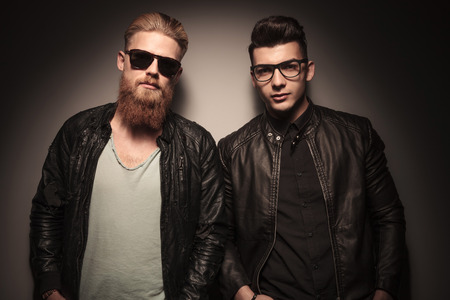 Two hot guys in leather jacket with glasses, looking at the camera, against studio background Stock Photo