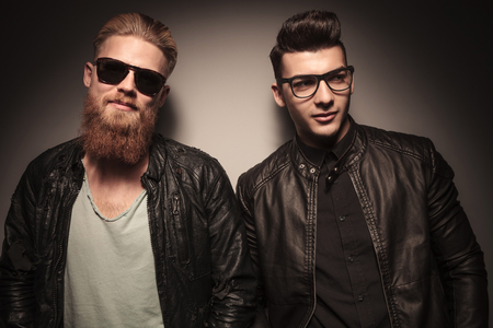 modelos hombres: Dos modelos de la moda masculina en la chaqueta de cuero que presentan contra el fondo del estudio, uno con gafas de sol y uno mirando a otro lado Foto de archivo