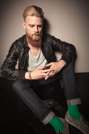 down sitting: Fasion man in leather jacket looking down, sitting and holding his hands, studio shot