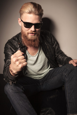 Cool guy with sunglasses in leather jacket challenging, one fist at the camera photo