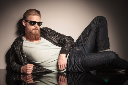 Male model in leather jacket and sunglasses, on the floor, looking at the camera