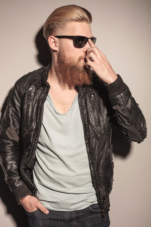 put away: Fashion man in leather jacket, fixing his sunglasses, looking away on gray studio background Stock Photo