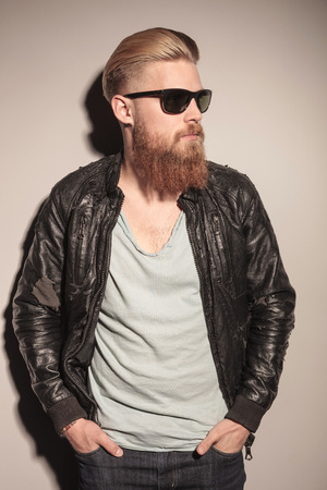 Casual young man with long red beard resting on the wall, with his hands in the pocket, looking away photo