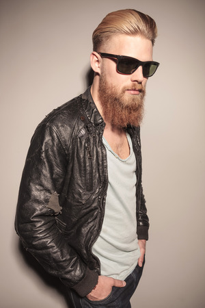 Angle view of a fashion young man in leather jacket with his hand in the pocket, looking away photo