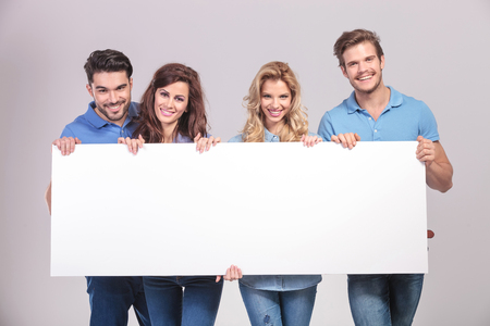 casual group of young people holding a big blank board on grey studio background photo