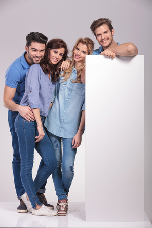 full body picture of four casual young people with a big blank billboard on grey background photo
