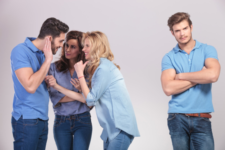 group of people making fun and gossip about their friend on grey studio background photo