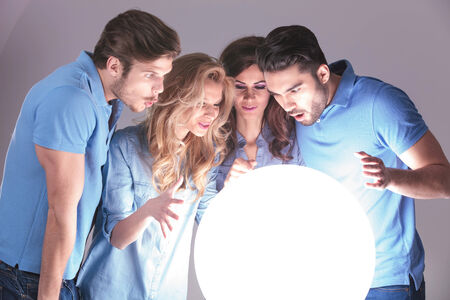 amazed group of people reading their future in a big ball of light photo