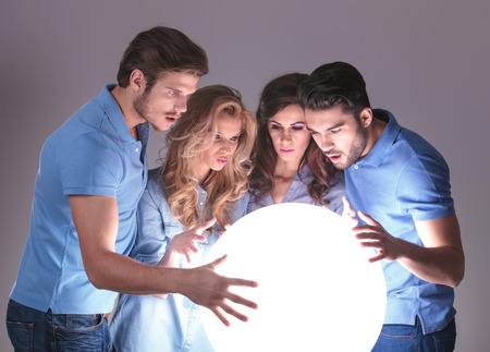 worried group of people reading about their future in a ball of light photo