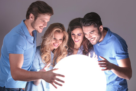 four friends: group of friends smiling and holding a big ball of light wich tells them their future