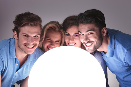 young casual people with faces close to a big ball of light and smile to the camera photo