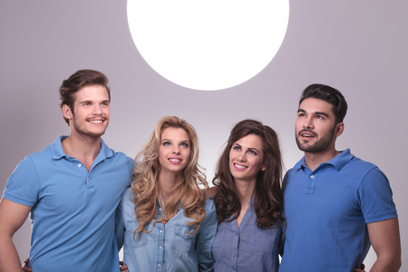 smiling group of casual people looking up into a big ball of light photo