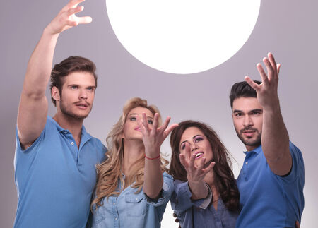 casual group of people reaching out for a big ball of light to tell them their future photo