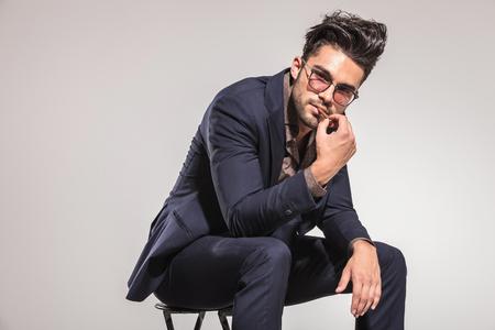 hombre sentado: hombre joven con estilo en traje sentado y pone su cigarrillo en la boca sobre fondo gris de estudio