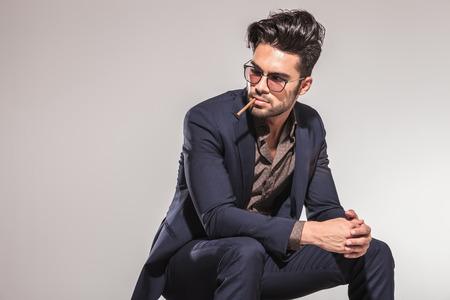 zijaanzicht van een mode-business man met een sigaret in zijn mond op zoek naar zijn kant Stockfoto