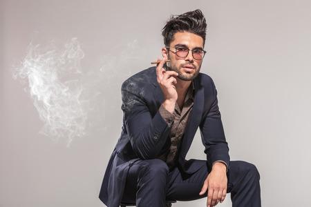 mode man in pak zittend op een stoel en roken, kijkend naar de camera op de grijze achtergrond studio
