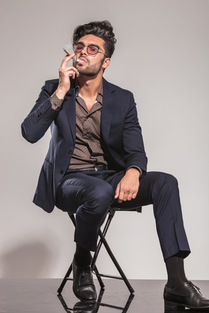 cigar smoke: cool guy enjoying his cigarette while sitting on chair on grey background Stock Photo