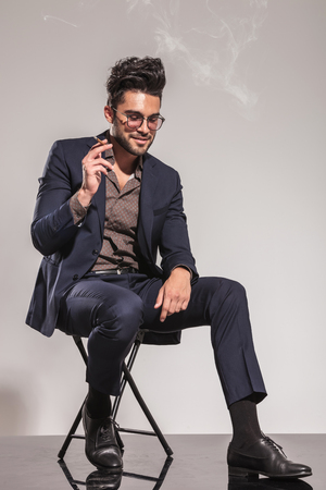 sitting down: seated young man in suit smoking cigarette and looks down on grey studio background