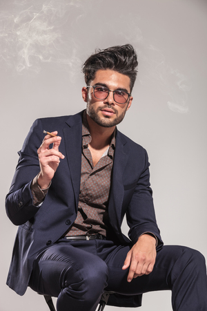 portrait of an elegant young man in suit smoking cigarette on grey studio background photo
