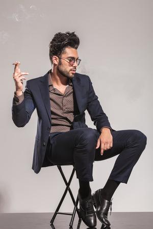 hombre sentado: lado de un hombre sentado en traje y gafas de fumar un cigarrillo y mira hacia otro lado Foto de archivo