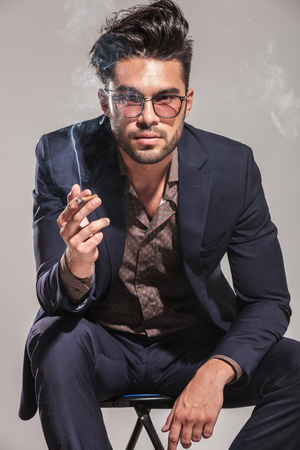 man in chair: young fashion man in suit and glasses smoking and sitting on grey background