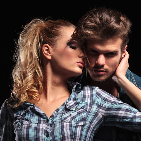 sexy couple black background: Picture of a blonde sexy woman looking away while holding her boyfriend close to her. The man is looking at the camera. Stock Photo