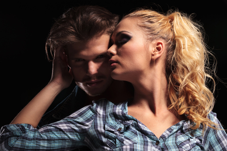 other side of: Picture of a blonde sexy woman looking away while she holds her hand behind her boyfriends head. Against black background. Stock Photo