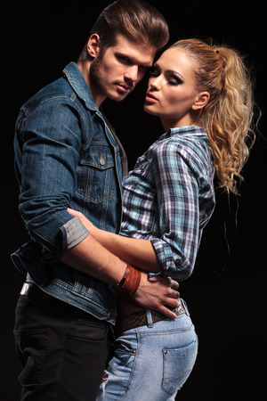 Handsome young man looking at the camera while he is embracing his blonde girlfriend, on black background.