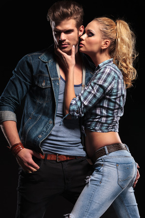 Hot blonde woman trying to kiss her boyfriend on the cheek. The man is holding one hand in his pocket, looking away.