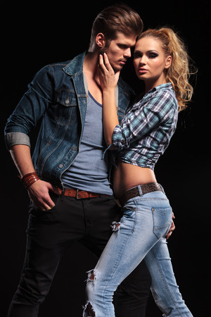 Attractive blonde woman posing for the camera while holding her boyfriend chin. The man is holding his hand in his pocket, looking away. photo