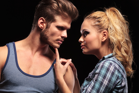 Close up of a blonde woman holding her boyfriend chin with he finger, looking at each other. On black background. photo