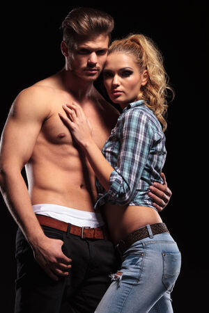 sexy topless women: Hot sexy blonde woman leaning on her topless boyfriend, both looking at the camera. On black background.