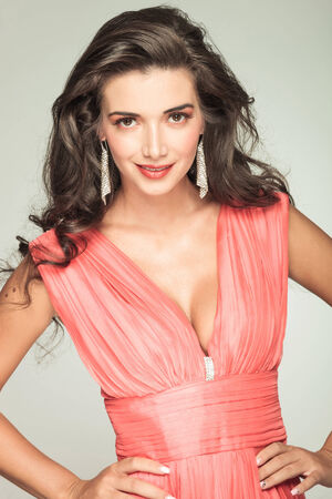 girl in red dress: happy attractive woman in red dress smiling with hands on hips on grey background