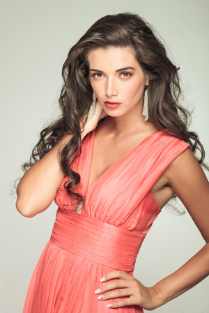 sexy woman in red dress holding her neck with hand and looks at the camera photo