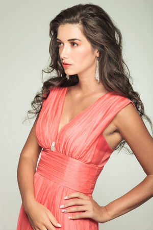 side view of an elegant woman in red dress looking away and standing with hand on hip in studio photo