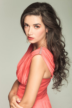 side of an attractive young woman in red dress with nice make up looking at the camera photo