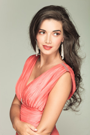 portrait of a smiling woman in red dress looking to her side on grey background photo