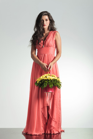 fashion young woman in elegant red dress holding a flower basket and looks to the camera on gray studio background photo