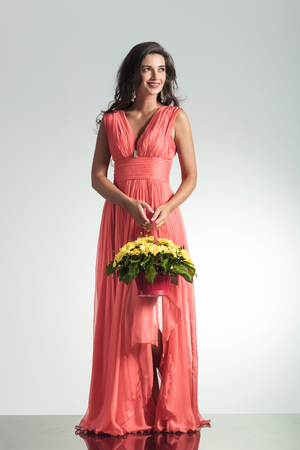 smiling elegant woman in red dress holding a flower basket and looks to side ongray background photo