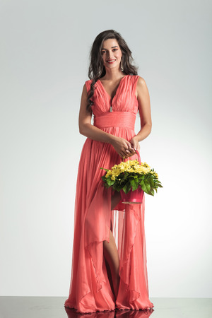 full body picture of a happy elegant woman in red dress holding a flower basket and smiles on gray background photo