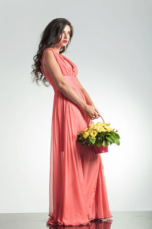 fashion woman in red dress holding a flower basket and poses in studio photo