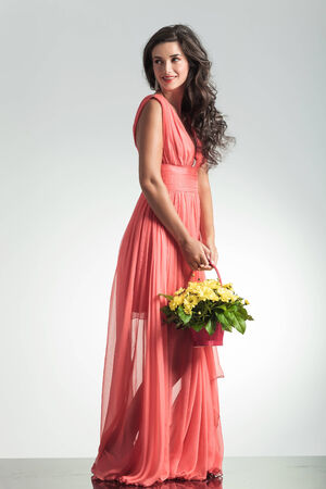 side view of an elegant woman in red dress looking away while holding a flower basket in studio photo