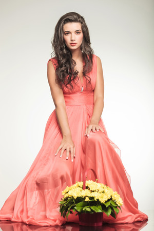 beautiful woman sitting near a yellow flowers basket and poses on grey studio background photo