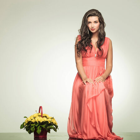 elegant sexy woman in red dress is sitting near a yellow flowers basket in studio photo