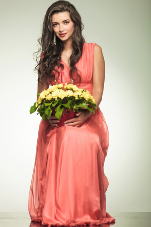 smiling woman in red dress holding a yellow flowers basket and sits on grey studio background photo